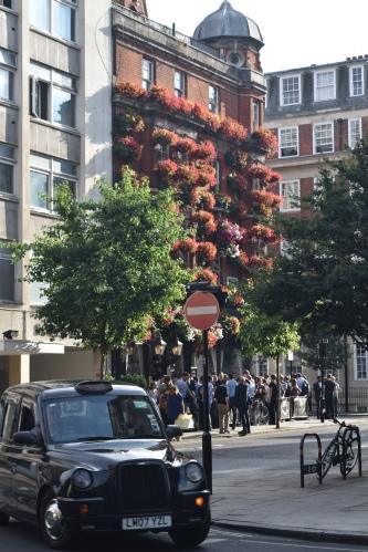 Cette photo résume à elle seule la ville : taxi typiquement londonien, gerbes de fleurs accrochées aux fenêtres et collègues de travail fêtant leur début de week-end en prenant un verre au bar du coin.